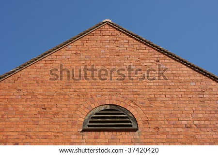 Brick wall with a pitched roof - stock photo