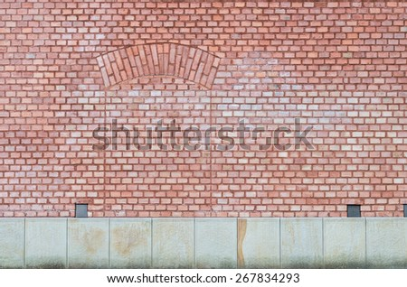 Brick wall with obsolete door bricked up on a stone foundation - stock photo