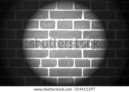 Brick wall with spotlight in black and white background - stock photo