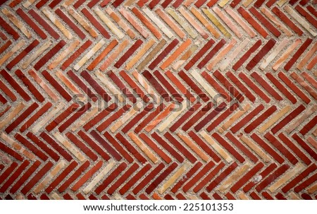 Brick wall with stones in Different shades of Red and Orange in a Herringbone Pattern - stock photo