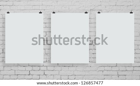 brick wall with three white poster - stock photo