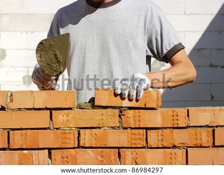 bricklayer laying bricks to make a wall - stock photo
