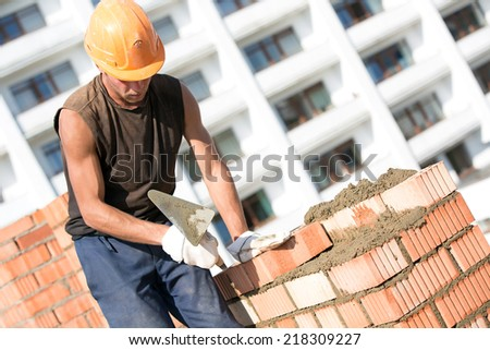 Bricklayer man worker installing brick with trowel during construction works - stock photo
