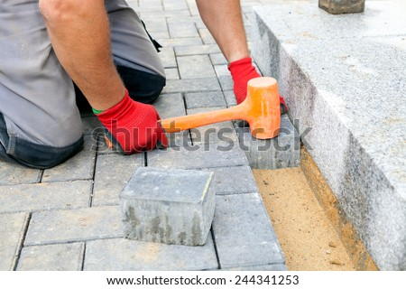Bricklayer places concrete paving stone blocks for building up a patio and a track in the backyard of a private house. - stock photo