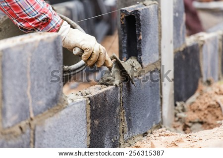 Bricklayer putting down another row of bricks in site - stock photo
