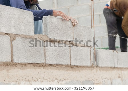 Bricklayer putting down another row of bricks in site.Selective focus. Very shallow Depth of Field, for soft background. - stock photo