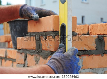 Bricklayer Using a Spirit  Level to Check New  Red Brick Wall Outdoor. Bricklaying Basics Masonry Techniques. - stock photo
