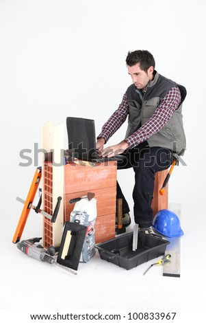 Bricklayer with a laptop - stock photo