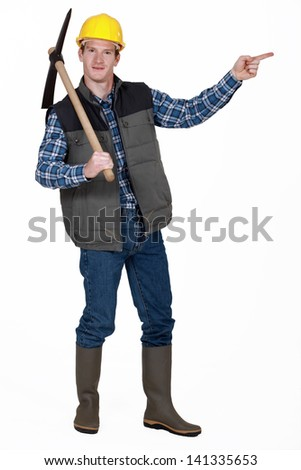 bricklayer with pickaxe pointing at something - stock photo