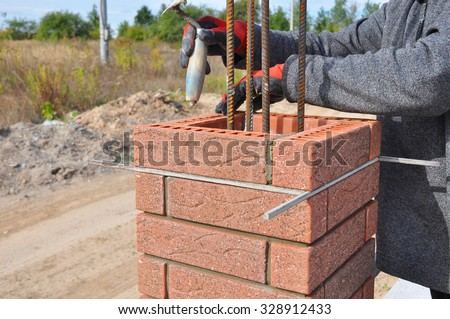 Bricklayer Worker Installing Red Clinker Blocks around Iron Bar and Caulking Brick Masonry Joints Exterior Wall with Trowel Putty Knife and Fixing with Spirit Level Outdoor - stock photo