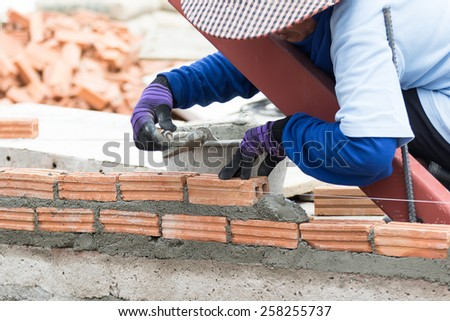 Bricklayer working in construction site of a brick wall. Bricklayer putting down another row of bricks in site - stock photo