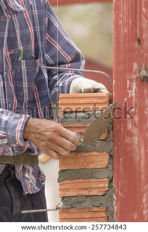 Bricklayer working in construction site of brick wall. Bricklayer putting down another row of bricks in site - stock photo