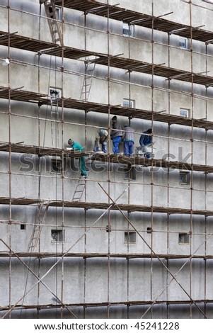 bricklayers workmen on scaffolding - stock photo