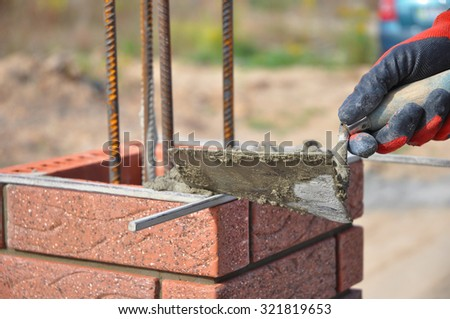 Bricklaying closeup. Bricklayer hand holding a putty knife and building a brick fence column. Building brick. - stock photo