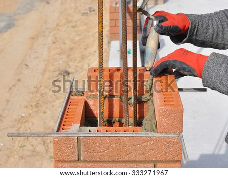 Bricklaying Closeup. Bricklayer hand holding a Putty Knife and Building a Brick Wall Column with Iron Bar Outdoor. - stock photo