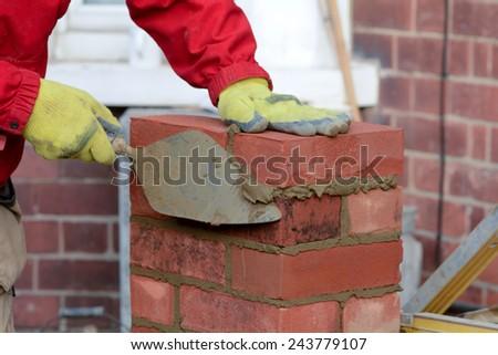 Bricklaying - laying brick and tidying render - stock photo