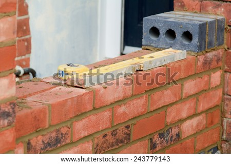 Bricklaying tools laying on top of red brick wall - stock photo