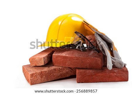 Bricks made of red clay,yellow hard hat, gloves and glasses on a white background - stock photo