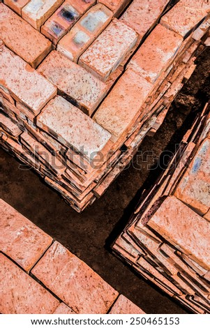 Bricks neatly stacked in square stacks by the building site. - stock photo