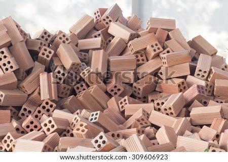 Bricks prepare for construction paste near the cement wall.  - stock photo