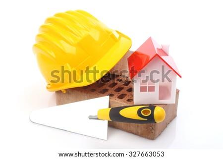 Bricks, trowel and helmet over white  - stock photo