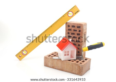 Bricks, trowel and level over white - stock photo