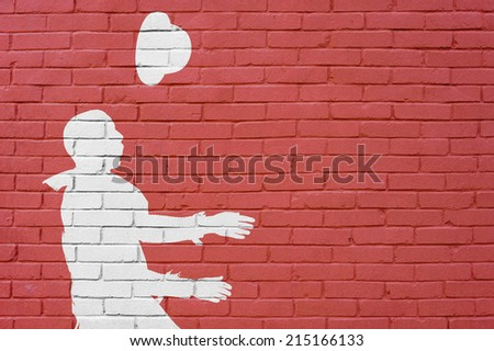 bricks wall with man throwing up his bowler hat on the air - stock photo