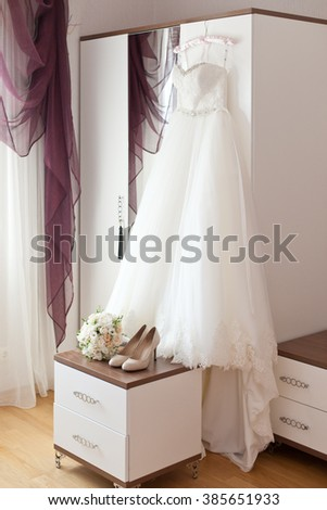 Bridal accessories: wedding dress, shoes and bride's bouquet - stock photo