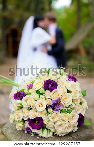 Bridal bouquet and the couple, bridal bouquet and the couple in the background - stock photo