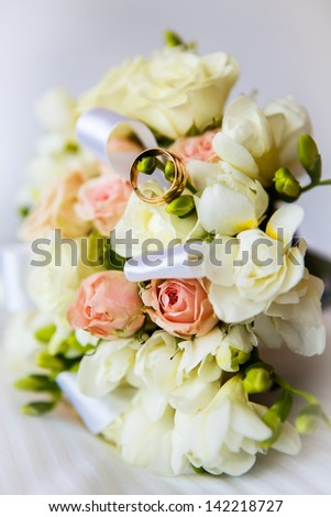 bridal bouquet and wedding rings - stock photo
