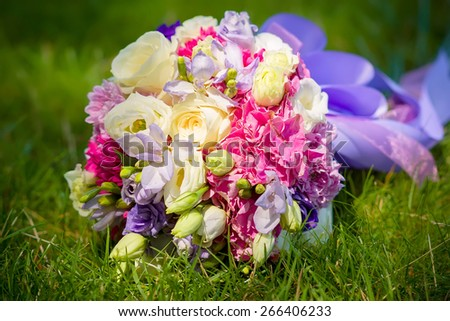 Bridal bouquet lying on the grass - stock photo