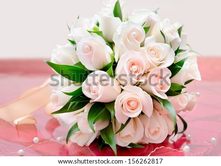 bridal bouquet of delicate light roses on red table - stock photo