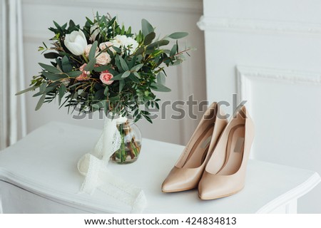 bridal bouquet of peones, wedding flowers for the ceremony on the chair in a hotel room with white shoes. - stock photo