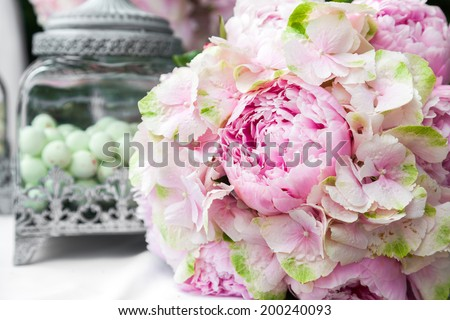 Bridal bouquet of peonies on bride and groom table at wedding reception - stock photo