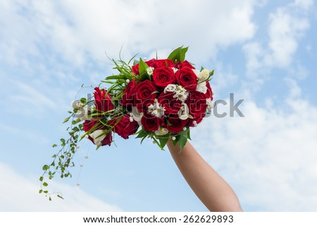 Bridal bouquet of red roses and white flowers held against the sky - stock photo