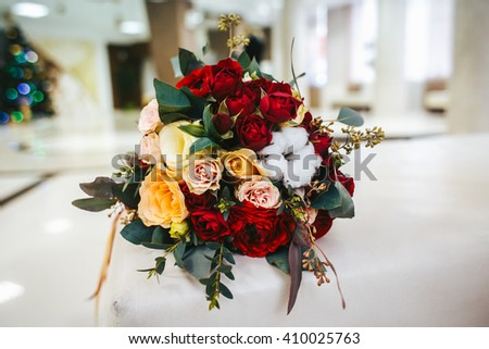 Bridal bouquet of roses and peony, red and yellow colors closeup view, abstract background. - stock photo