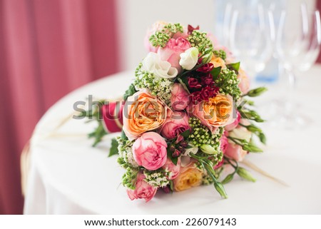 bridal bouquet of roses, buttercups and other flowers on the table - stock photo