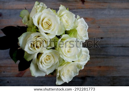 bridal bouquet of roses on a wooden background - stock photo