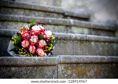 bridal bouquet of roses on the steps of the church - stock photo