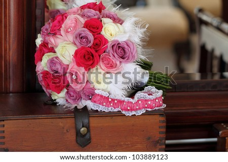 Bridal bouquet of roses on wooden vintage style box, pink and white garter in the foreground - stock photo