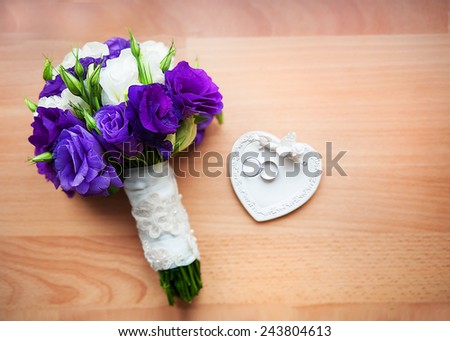 bridal bouquet of roses, peony and rings on a saucer in the form of heart. - stock photo