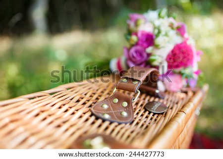Bridal bouquet on a suitcase in a park - stock photo