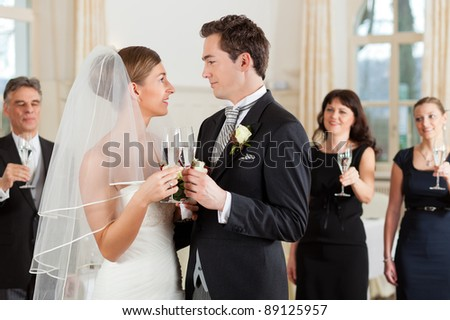 Bridal couple clinking glasses while the guests standing in the background - stock photo