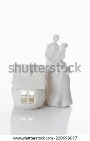 Bridal couple figurine and house - stock photo