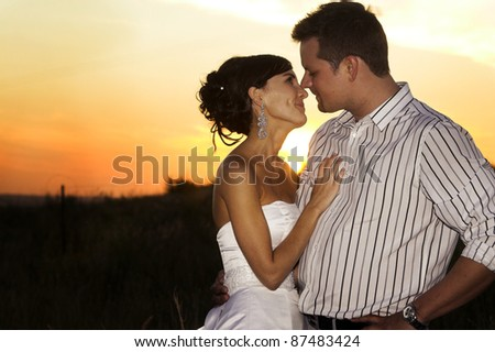 Bridal couple in the field as the sun sets - stock photo