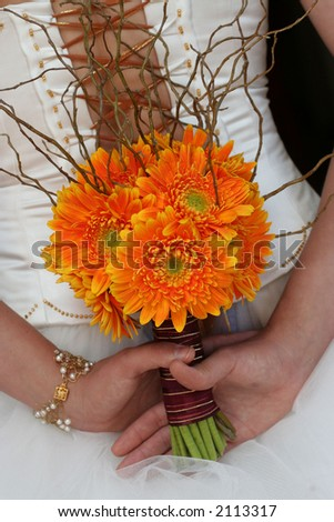 Bridal flower bouqeut being held behind brides back - stock photo