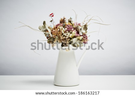 Bridal flowers dried in vase on white table top - stock photo