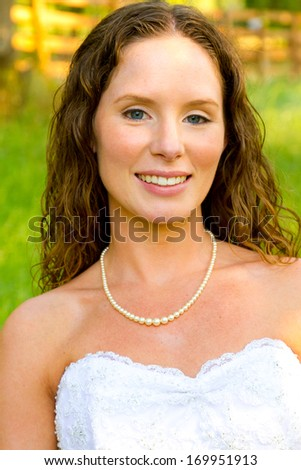 Bridal portraits of this beautiful bride on her wedding day wearing a traditional yet fashionable white wedding dress. - stock photo