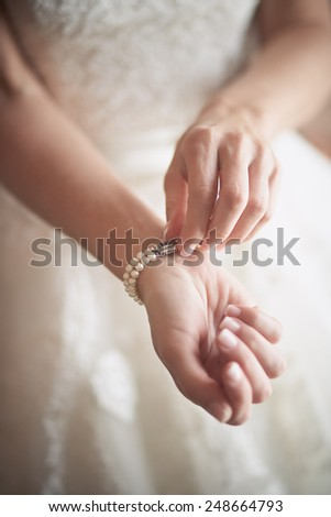 Bridal preparation, bride putting on jewelry, focus on bracelet  - stock photo