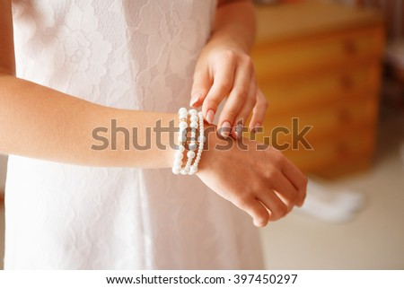 Bridal preparation for the wedding ceremony. bride putting on jewelry - stock photo